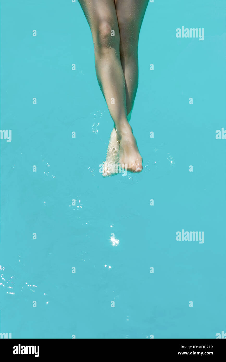 Young woman dangling legs in pool, cropped view - Stock Image