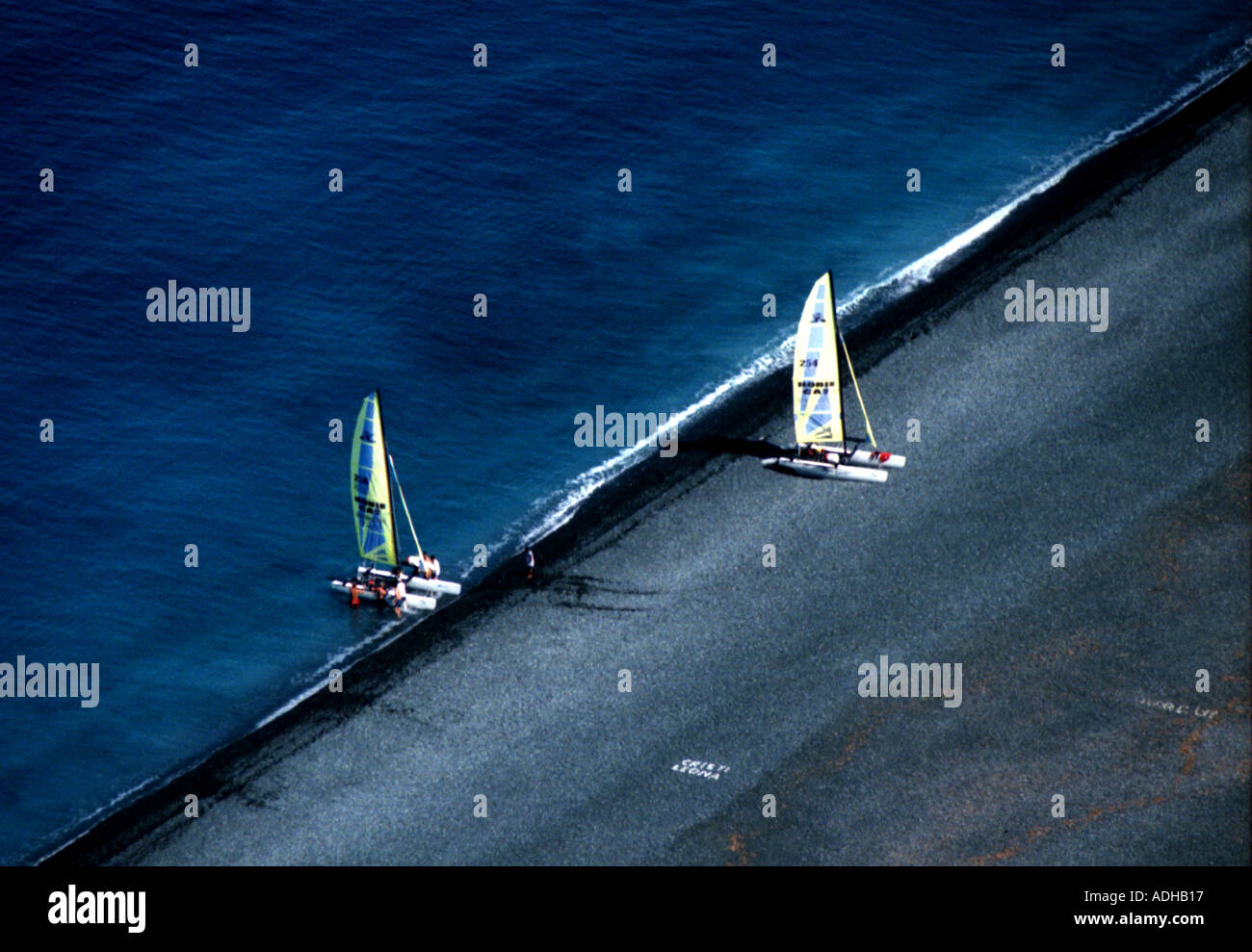 Two catamarans casting off onto the Mediterranean from black stone man made beach in Corsica Stock Photo