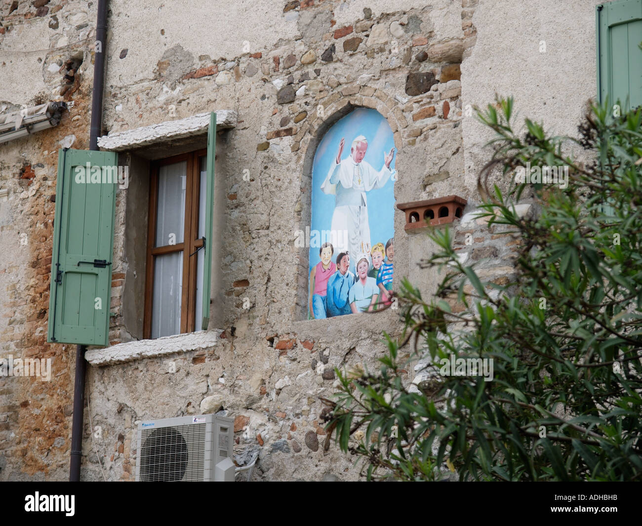Portrait image of pope John Paul II with children on an old house in Sirmione Italy - Stock Image