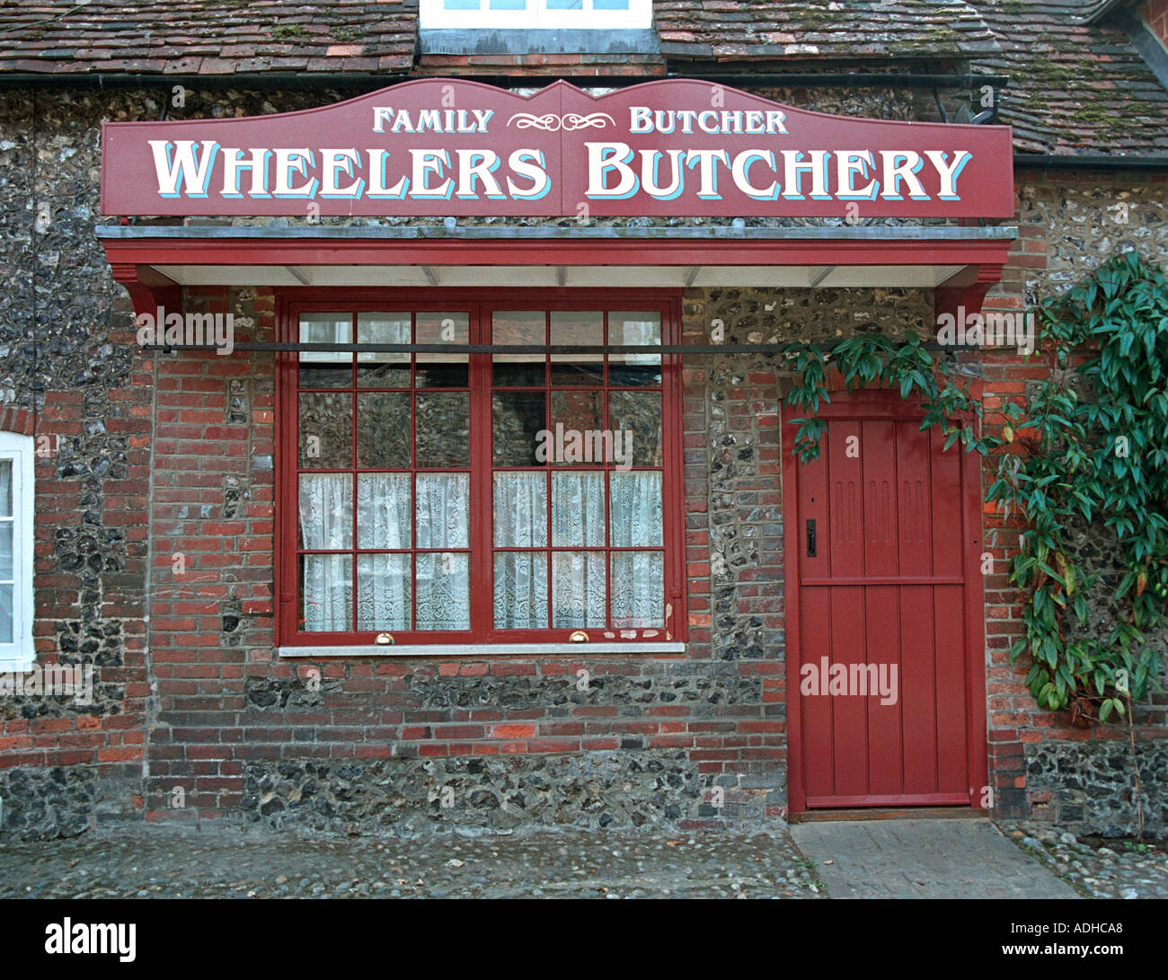 Local butcher in an English village scene of many films and TV shows - Stock Image