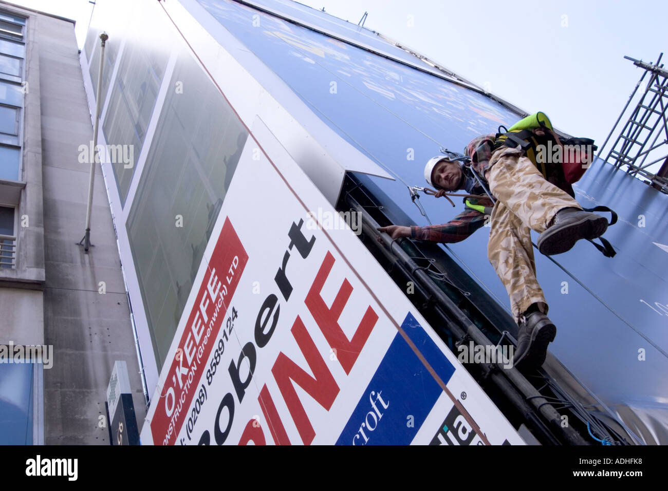 Dangerous occupations RAT roped access technician abseiler on advertising hoarding oxford street - Stock Image