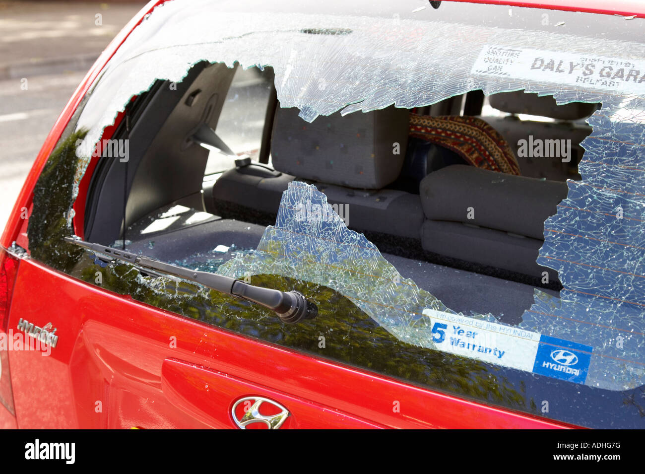 shattered rear window of red hyundai car damaged by vandals - Stock Image