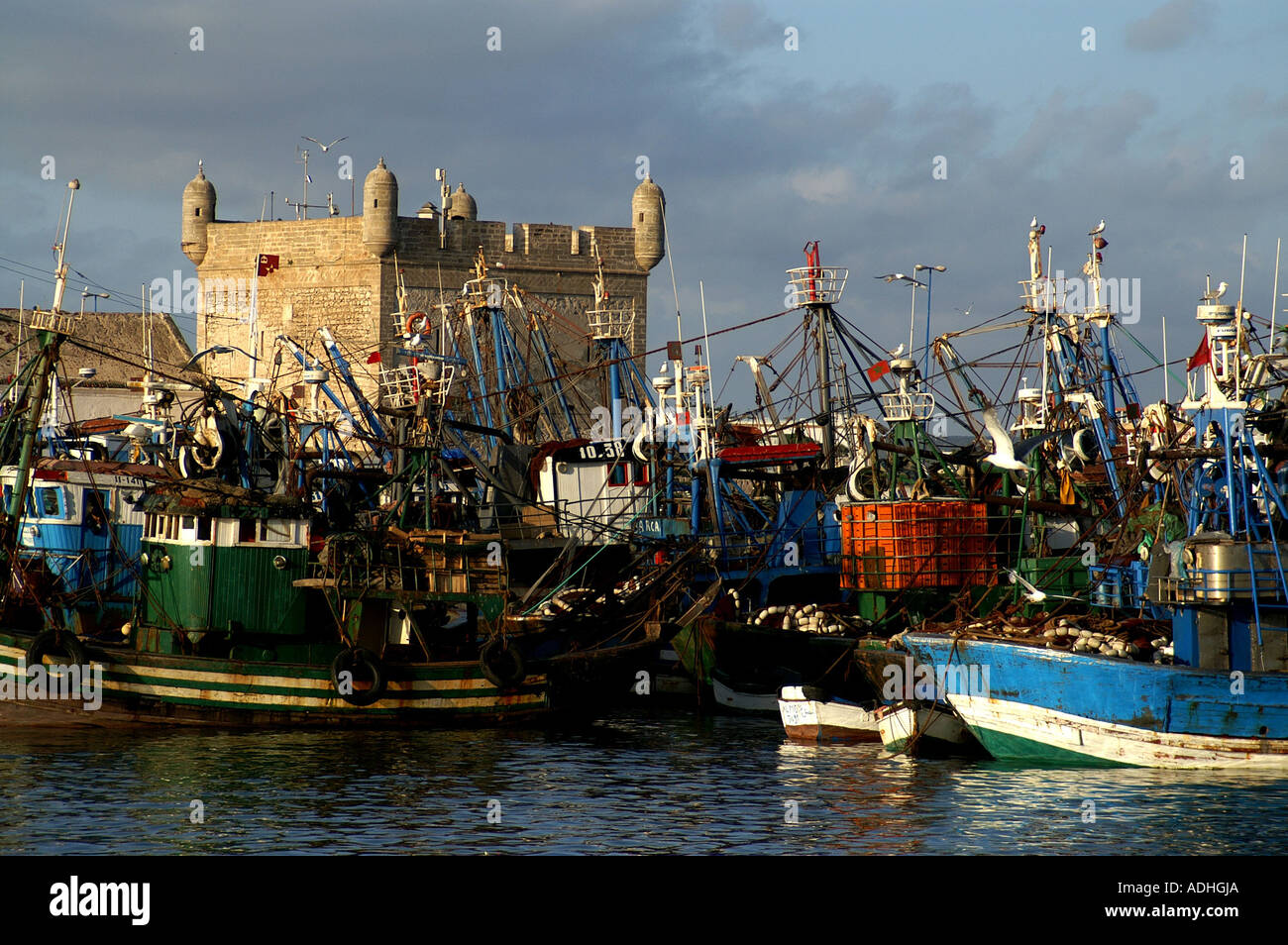 Fishing boats and craft by Turret Sqala du Port harbour Essaouira Morocco - Stock Image