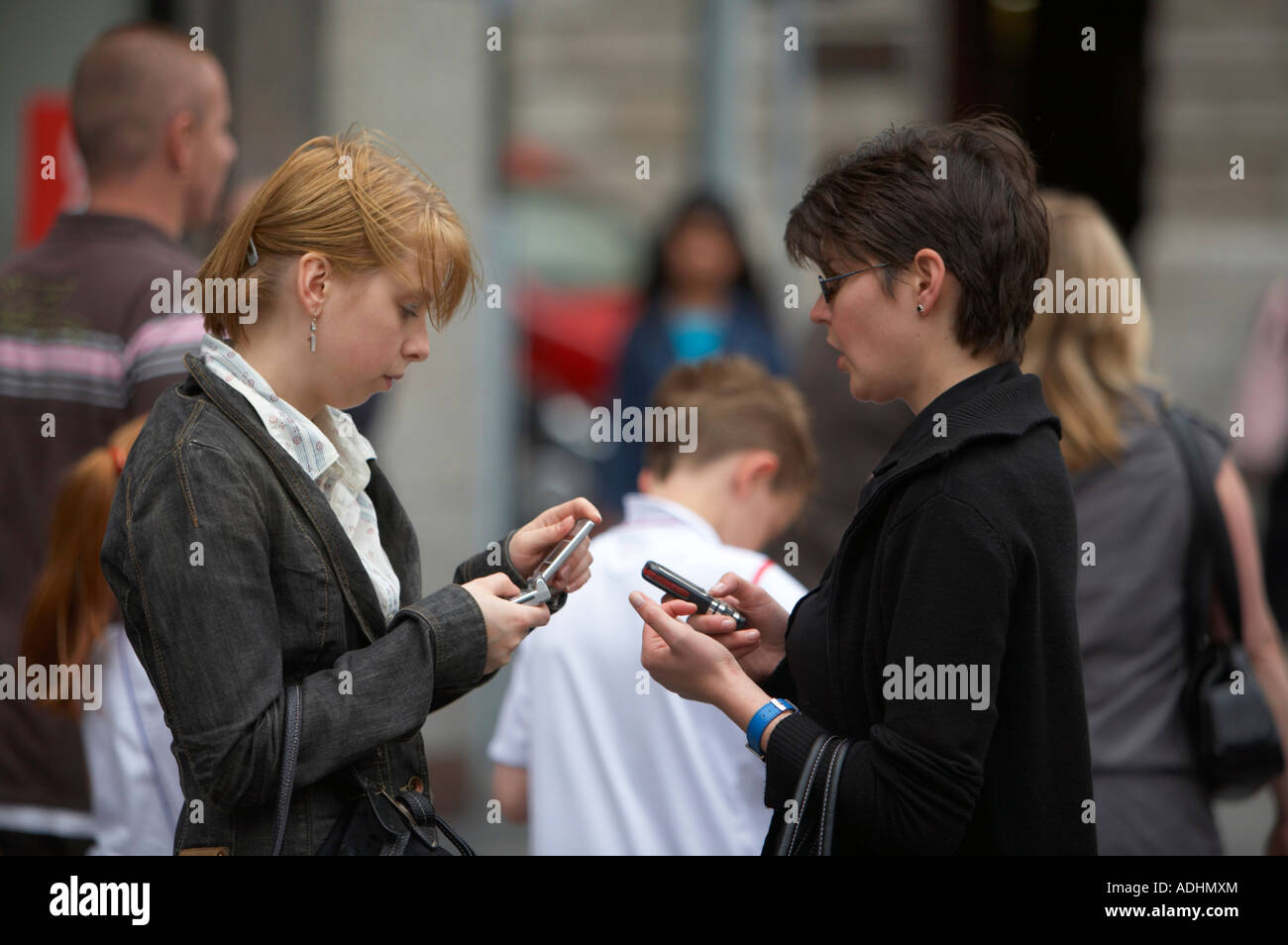 two women exchange phone numbers from mobile phones on crowded street in central dublin - Stock Image