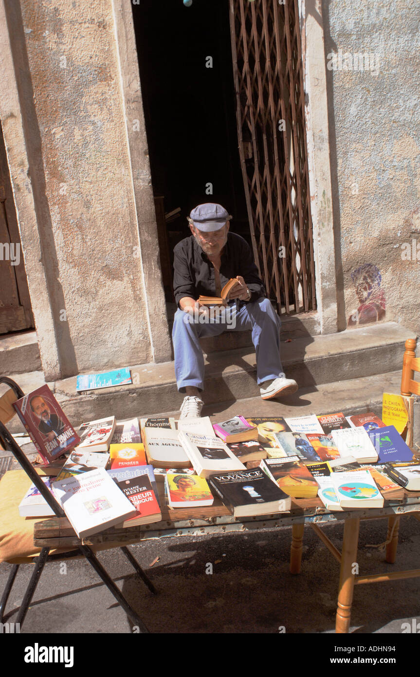 France Marseille Informal used book seller and reader in Le Panier district west of Le Vieux Port - Stock Image
