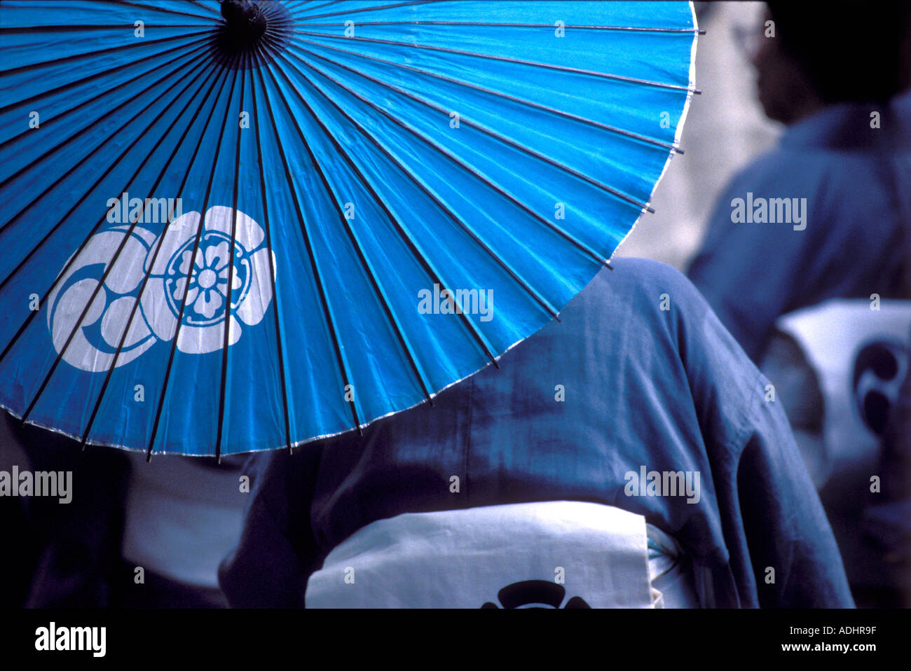 Woman wearing kimono carries a traditional blue paper and bamboo umbrella with a family crest - Stock Image