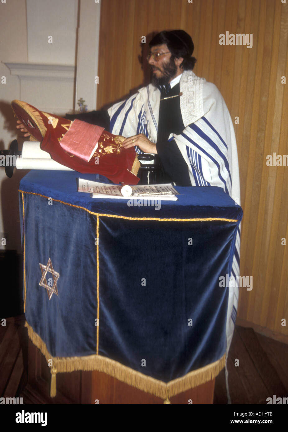 A British rabbi reading from the torah in a Reform Synagogue in south London - Stock Image