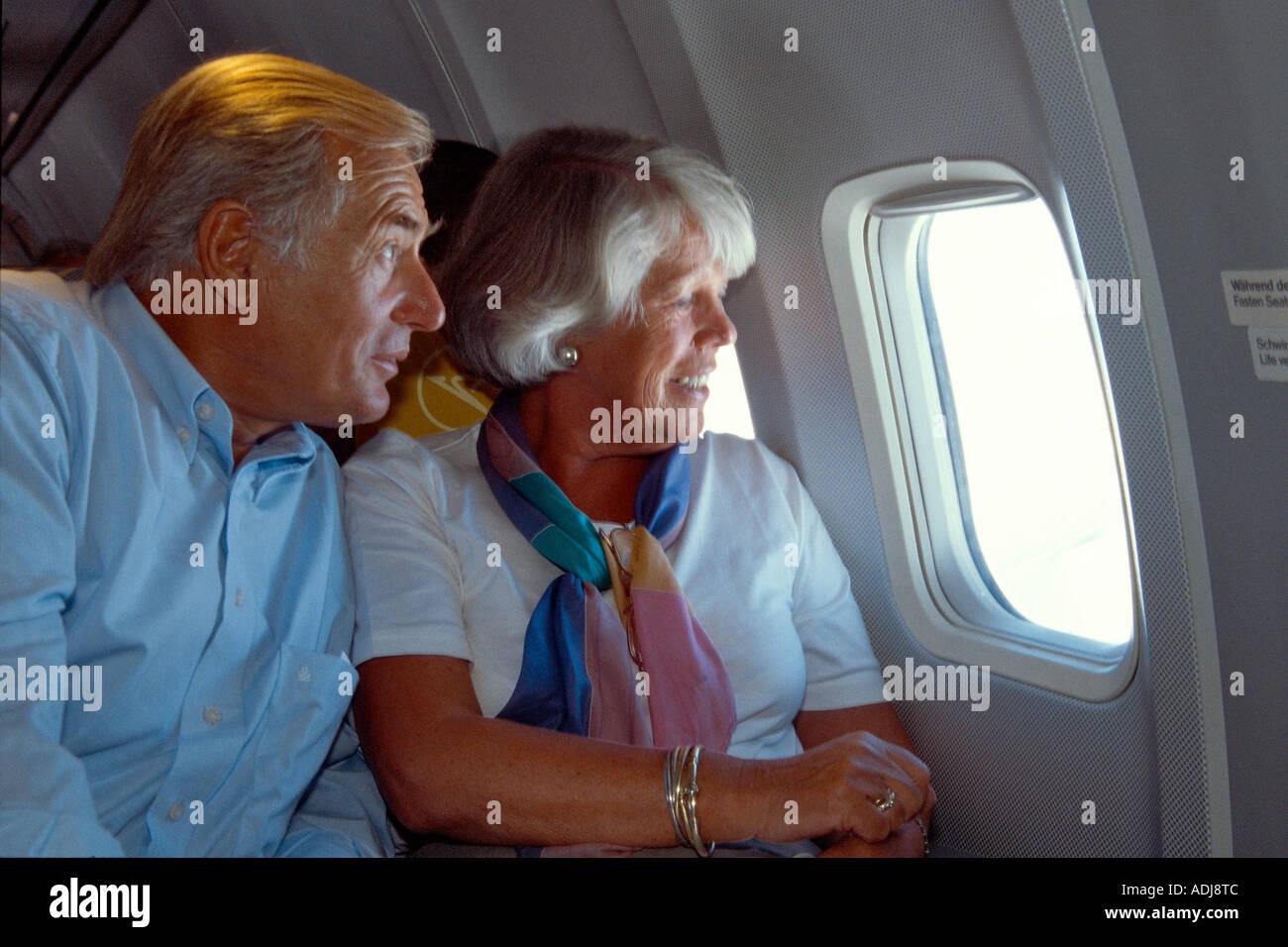 Seniorenpaar im Flugzeug aus dem Fenster schauend Stock Photo
