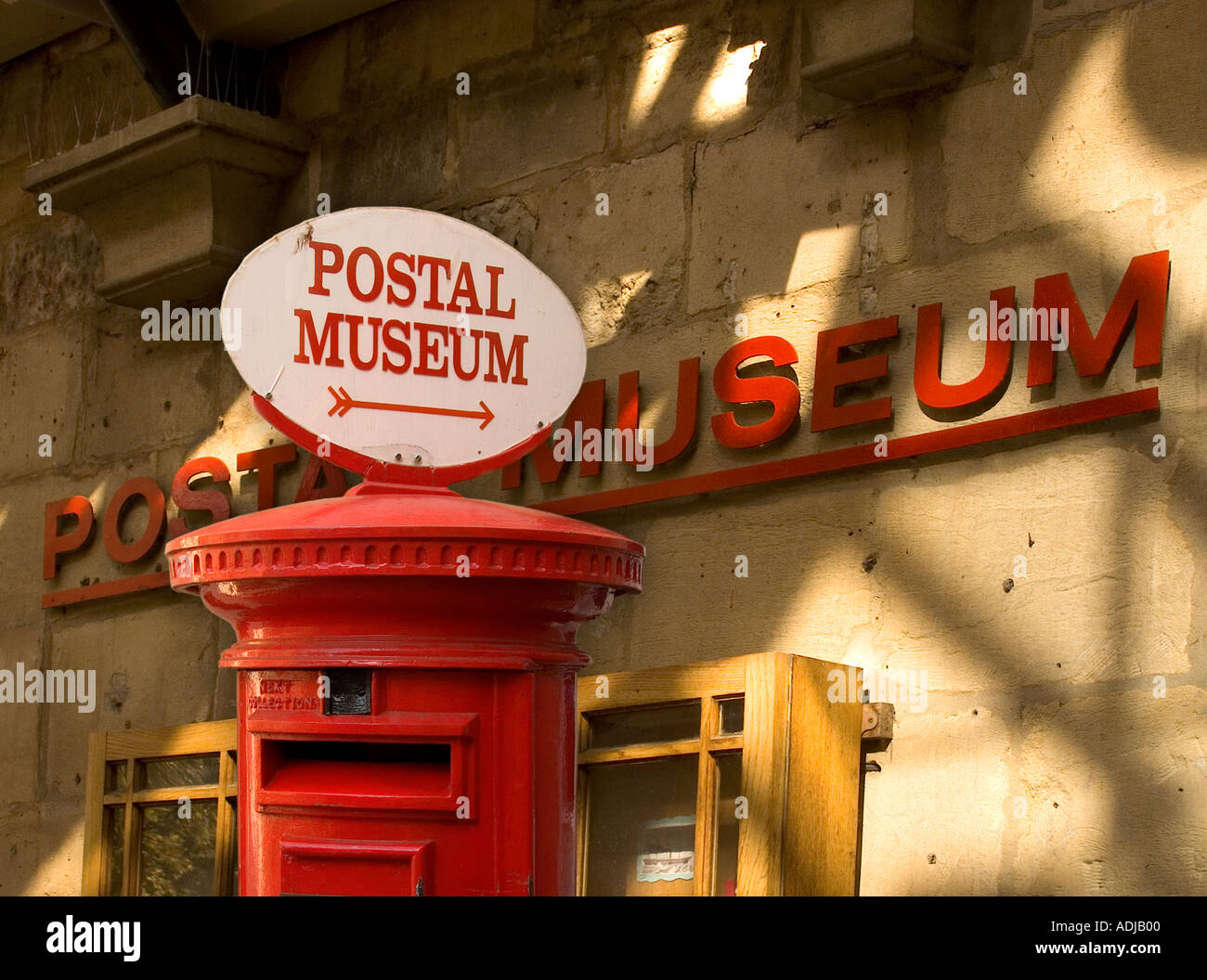 Red pillar box with sign to The National Postal Museum, exterior behind is earlier museum address at 8 Broad Street, Bath, Avon, UK - Stock Image