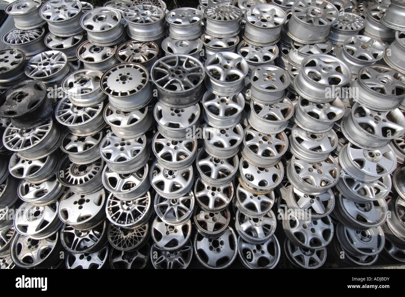A pile of discarded second hand alloy car wheels at a scrapyard awaiting recycling - Stock Image