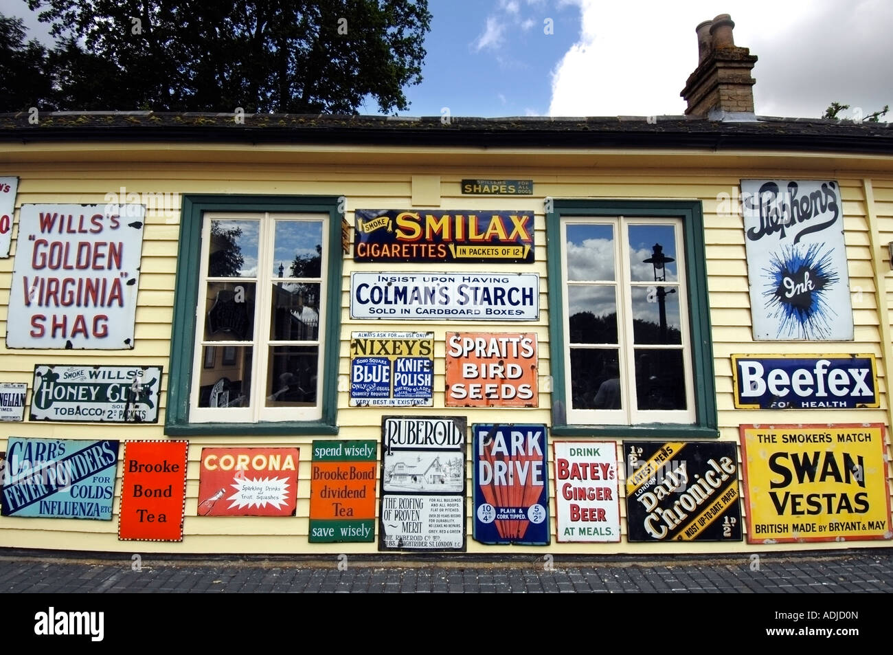 Old fashioned enamel advertising signs dating from 1920 to 1960 on a Victorian station at a railway museum - Stock Image