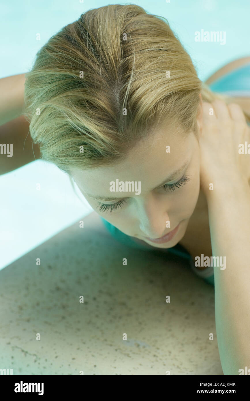 Woman lying by pool, hands behind neck, close-up - Stock Image