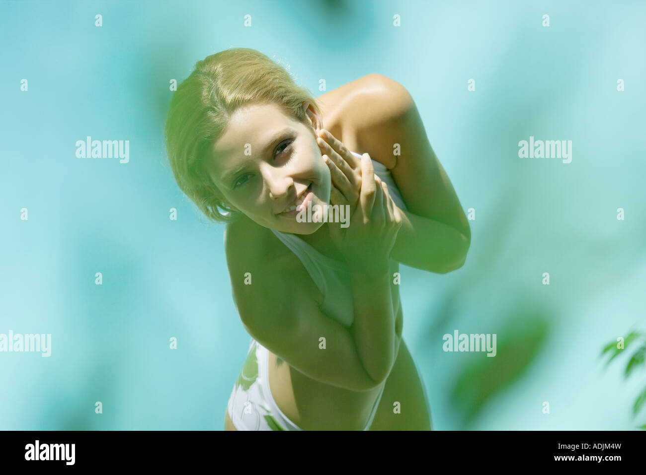 Young woman standing in bikini, high angle view, blur in foreground - Stock Image