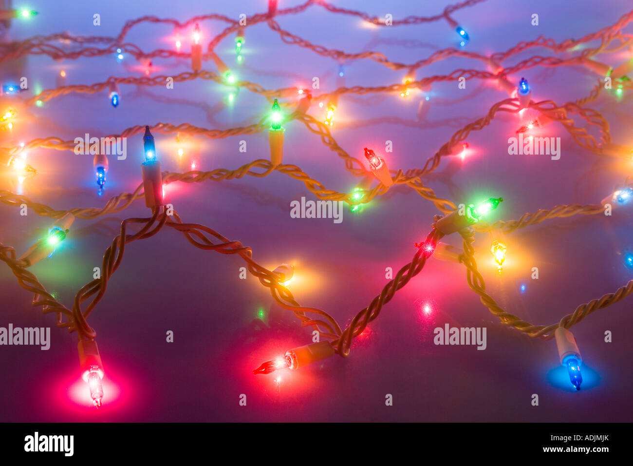 Web of multiple strands of multi colored Christmas tree lights in dimmed studio portrait - Stock Image