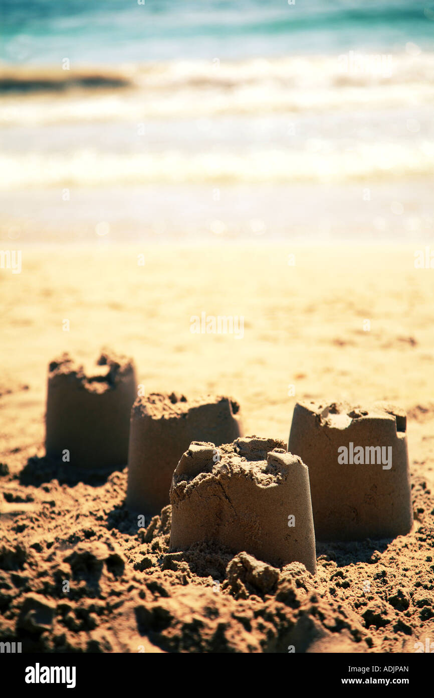 Four sandcastles on the beach with the sea in the background - Stock Image