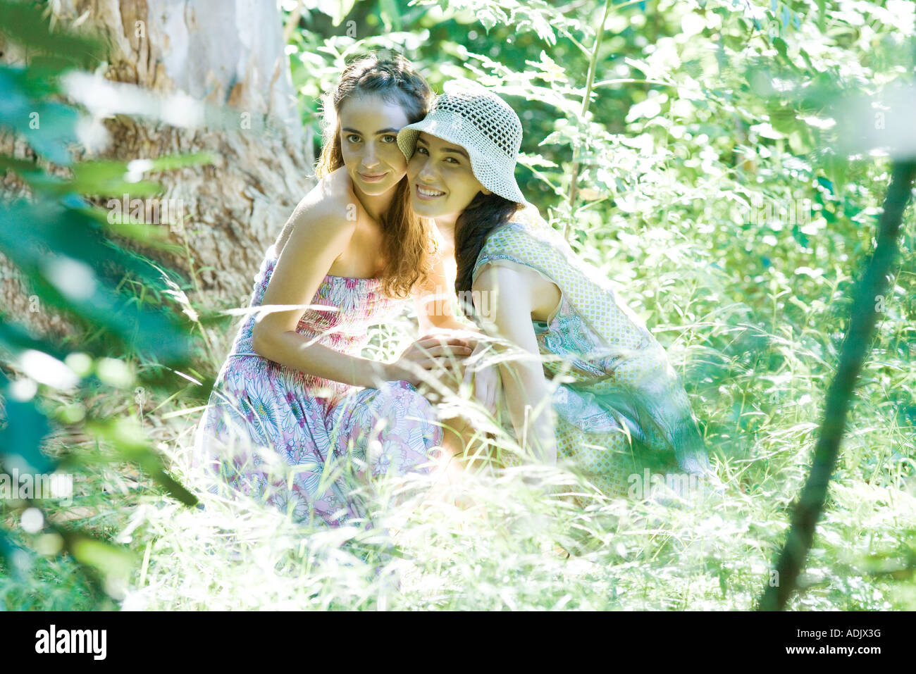 Two young women wearing sun dresses, crouching near tree with cheeks together, looking at camera - Stock Image