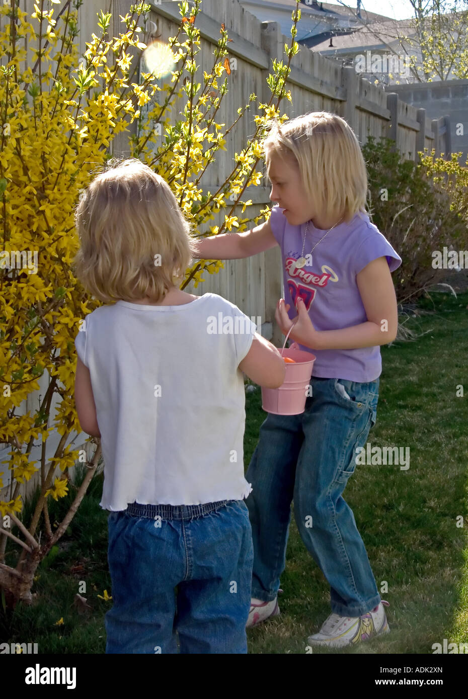 Young girls have found more treasures on their search for more Easter eggs in a backyard Easter egg hunt in Utah, Stock Photo