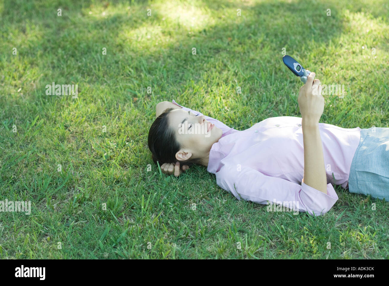Businesswoman lying in grass, looking at cell phone - Stock Image