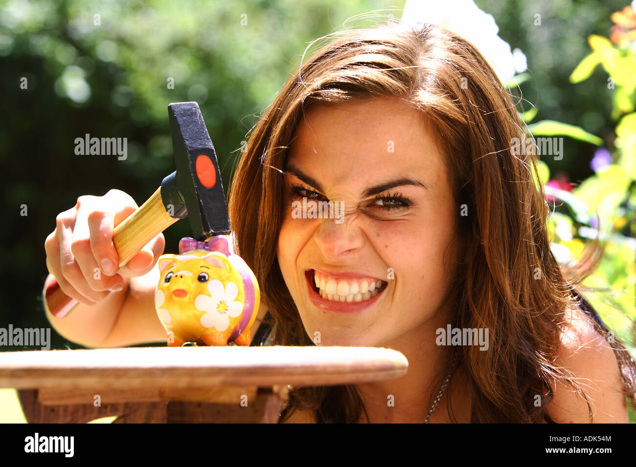 Young woman is robbing a piggy bank with a hammer © Peter Schatz/Alamy - Stock Image