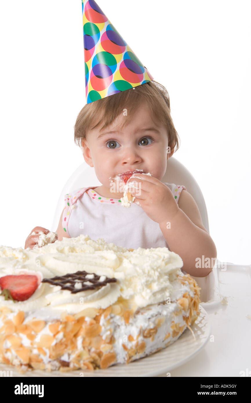 One year old baby girl eating from her birthday cake Stock Photo