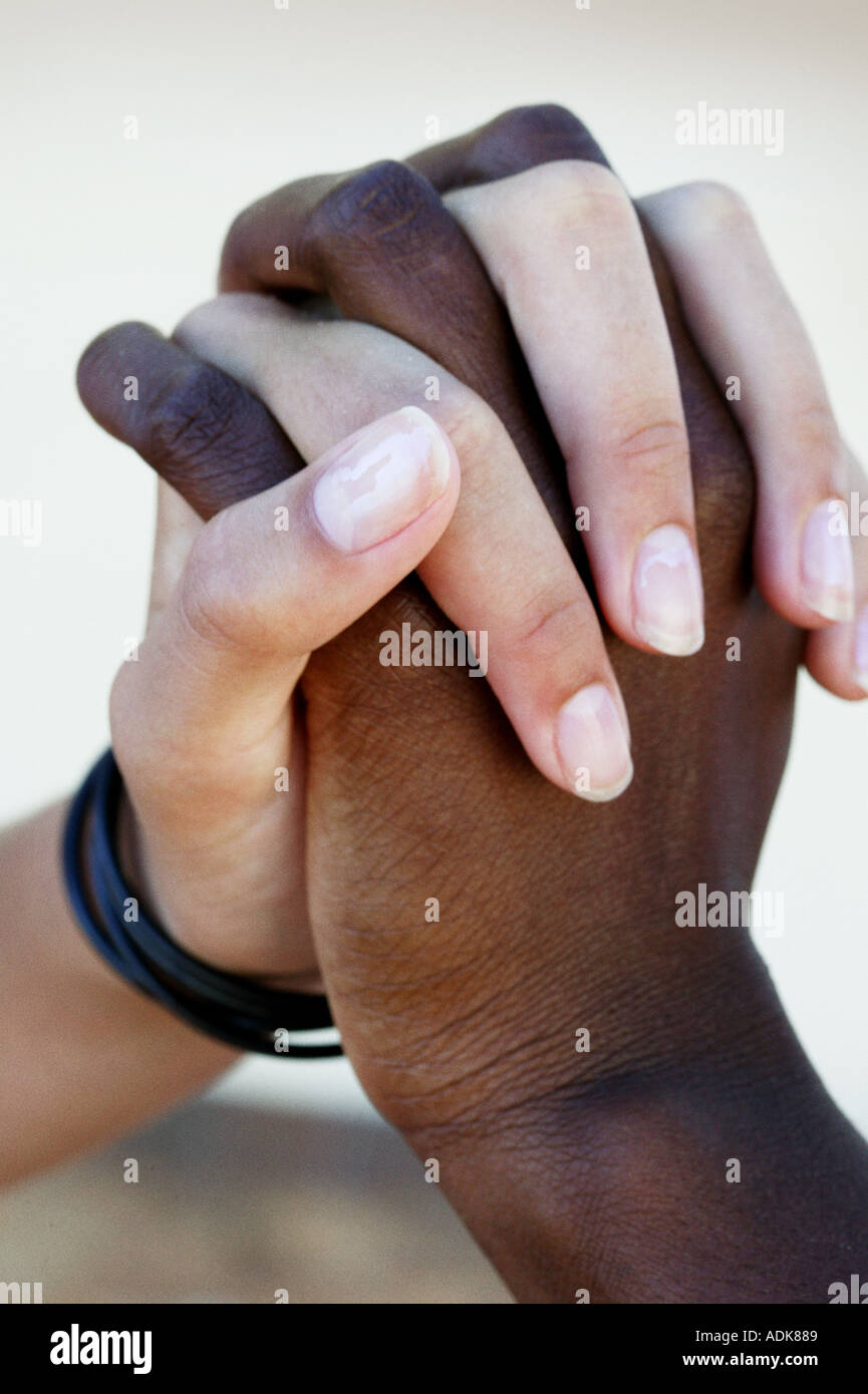 Black and white hands interlinked - Stock Image