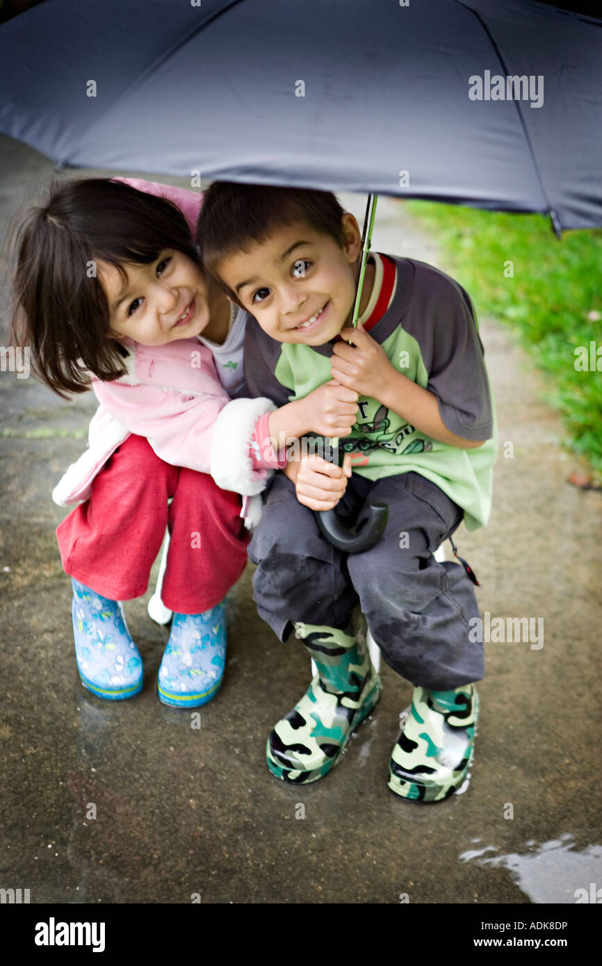 Brother and sister shelter together under umbrella - Stock Image