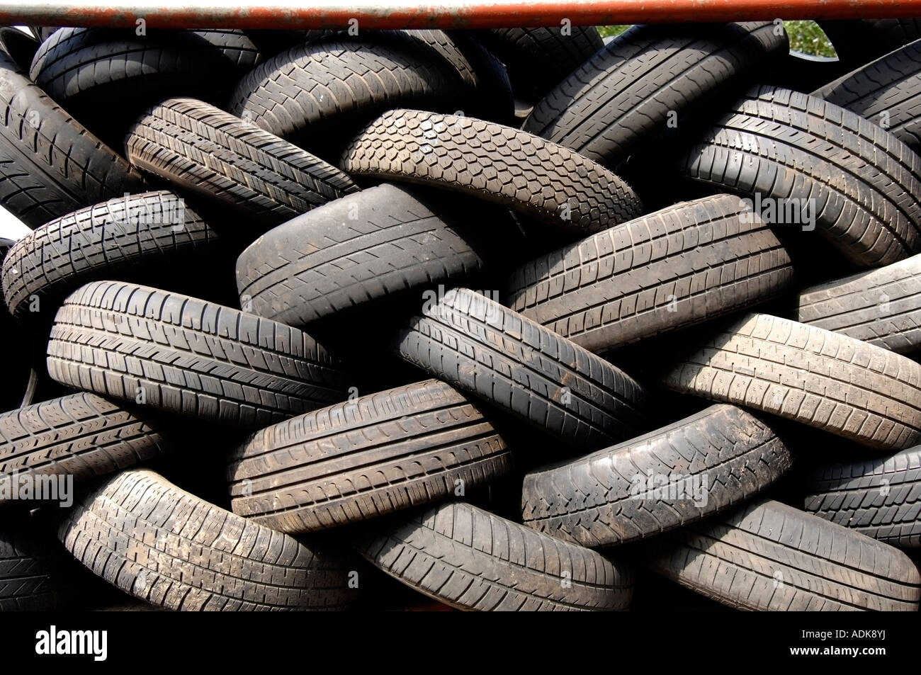 Worn out car tyres at a scrapyard wait to be shredded and recycled - Stock Image