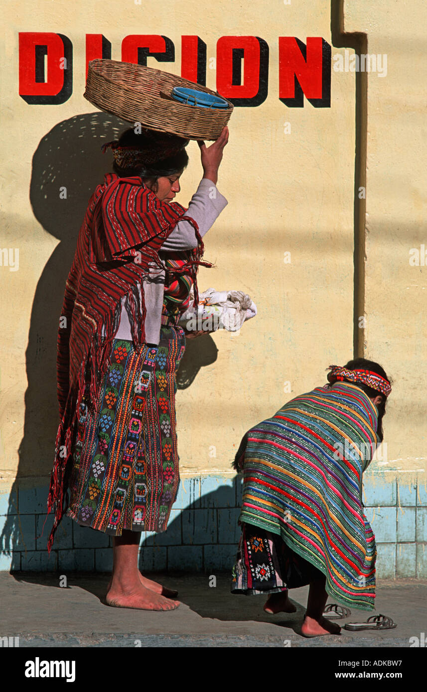 GUATEMALA Mother stops as her child pauses to slip her shoe on Walking from market Zunil Guatemala - Stock Image