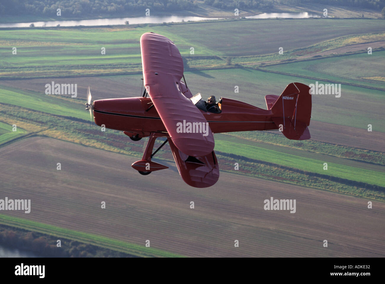 Red Bi wing Plane Flying Over Fields - Stock Image