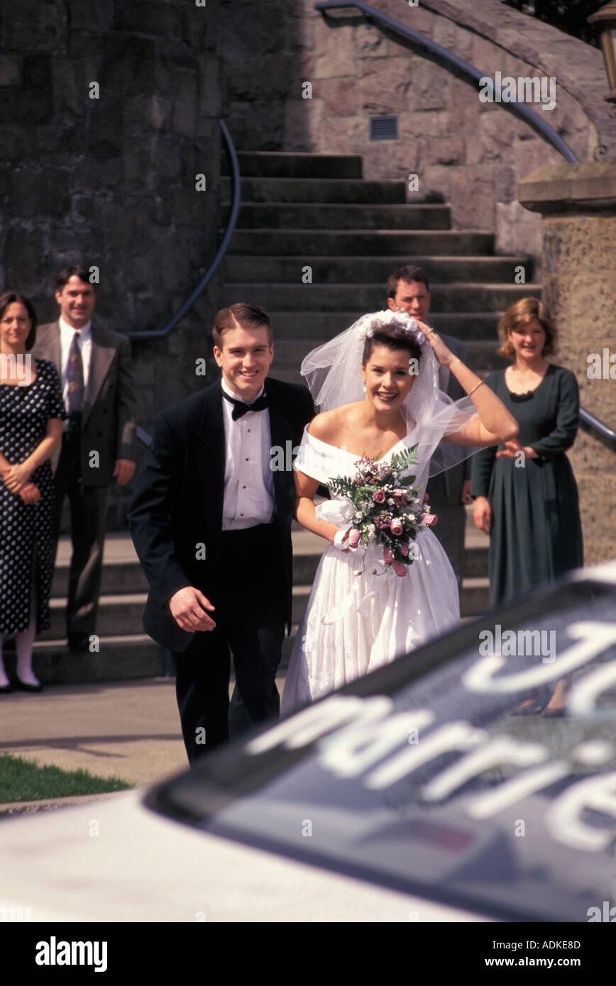 Bride And Groom Running Toward Getaway Car - Stock Image