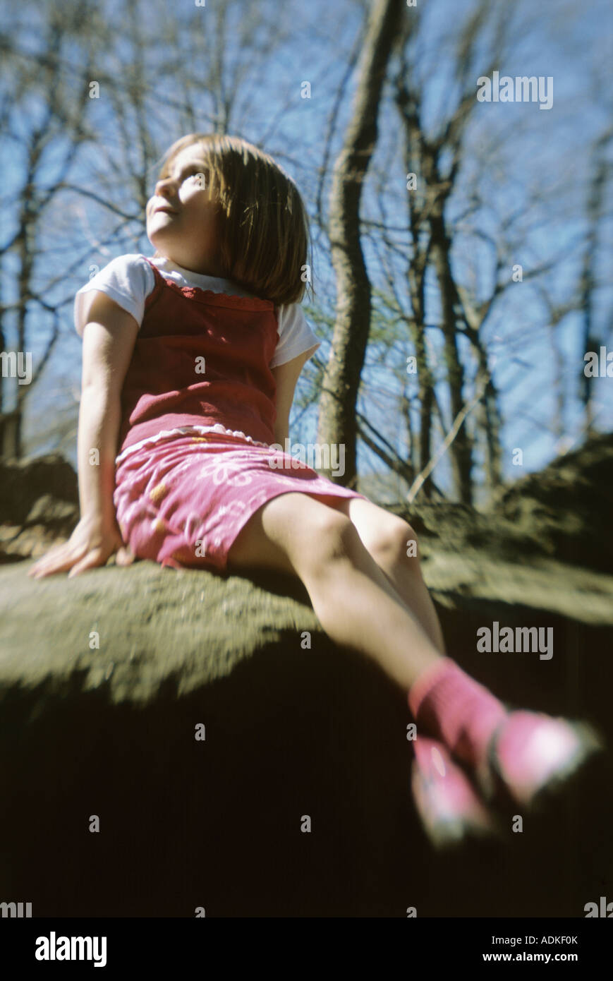 Little girl sitting on rock at park, looking upward - Stock Image