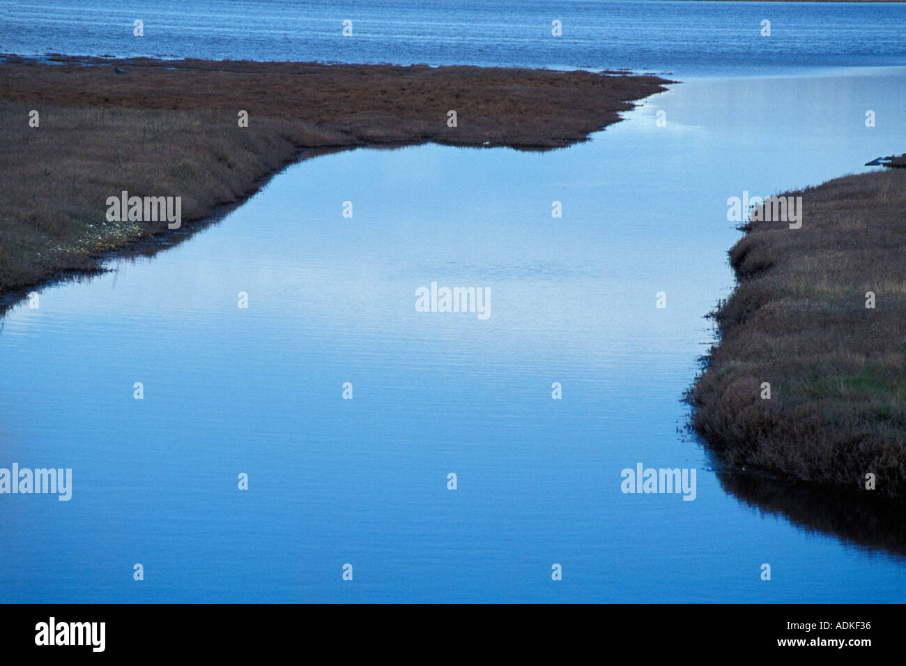Canal Flowing Into Large Body Of Water - Stock Image