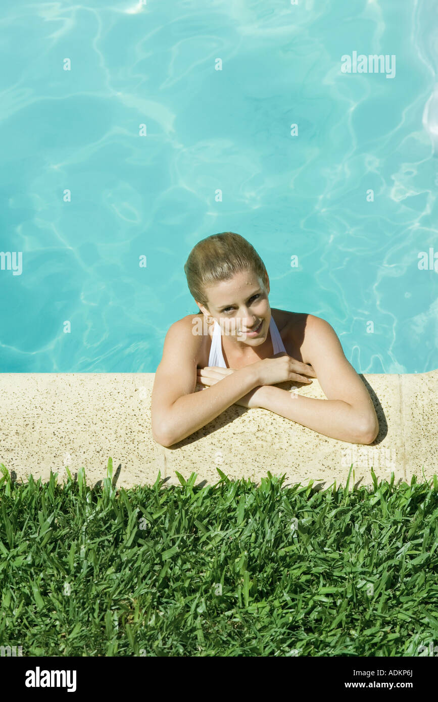 Young woman resting arms on edge of pool - Stock Image