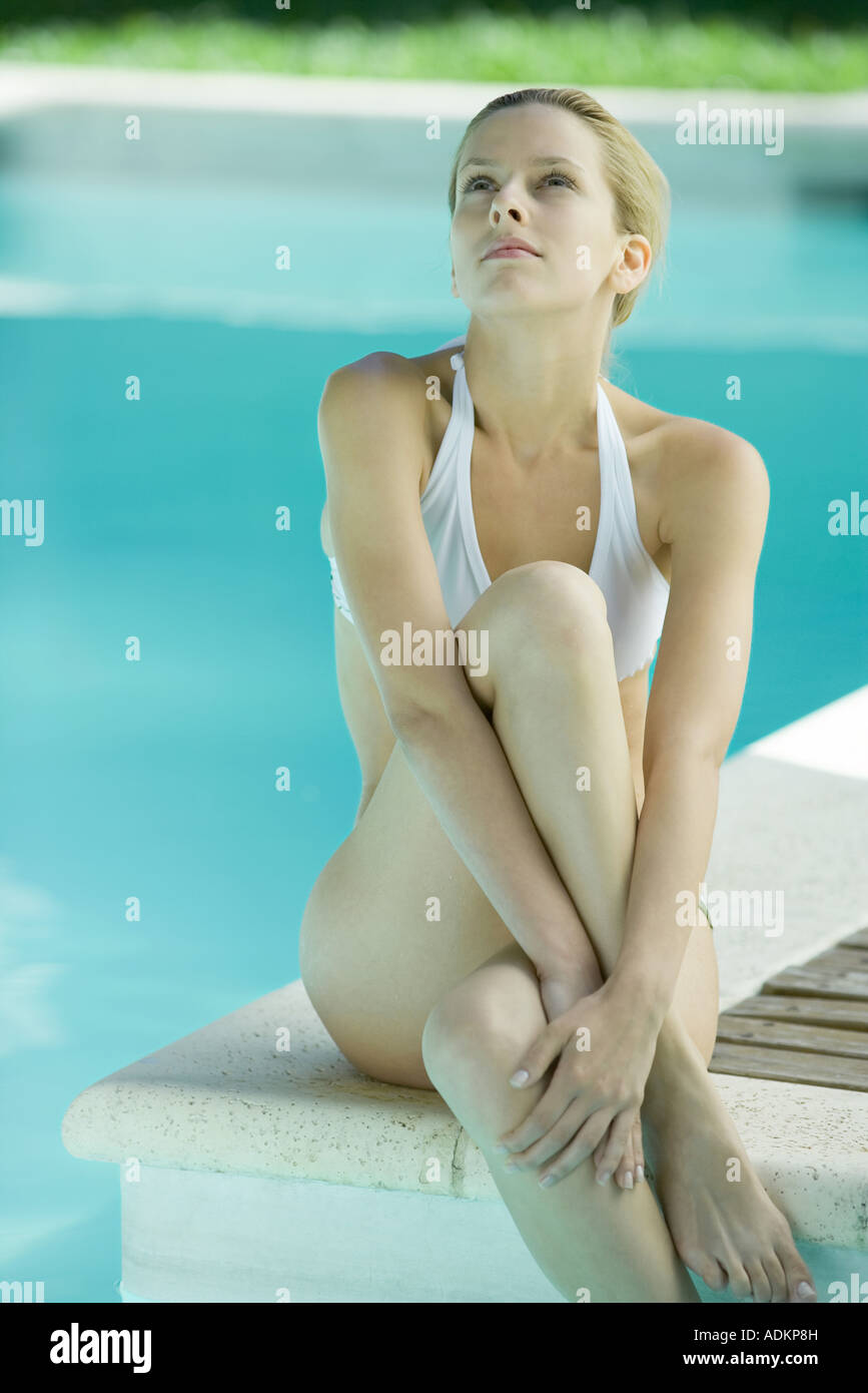 Young woman sitting on edge of pool, legs crossed, looking up - Stock Image