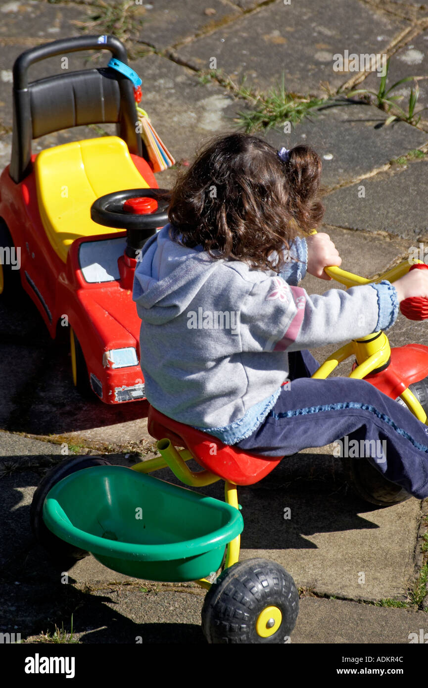 Young girl playing outside on a tricycle - Stock Image
