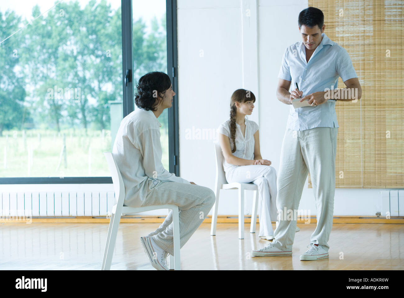 Group therapy, two adults sitting while one man stands, writing on notepad - Stock Image