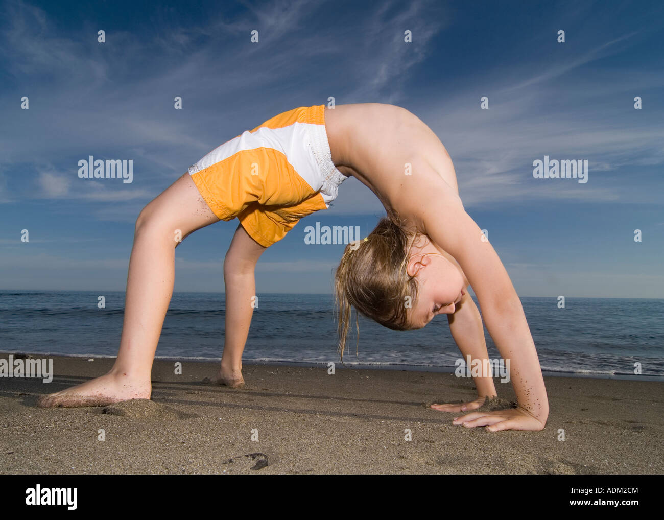 young girl exercising on the beach - Stock Image