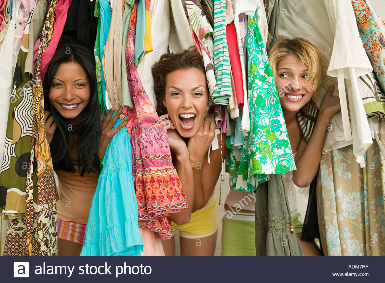 Friends looking through hanging clothes - Stock Image