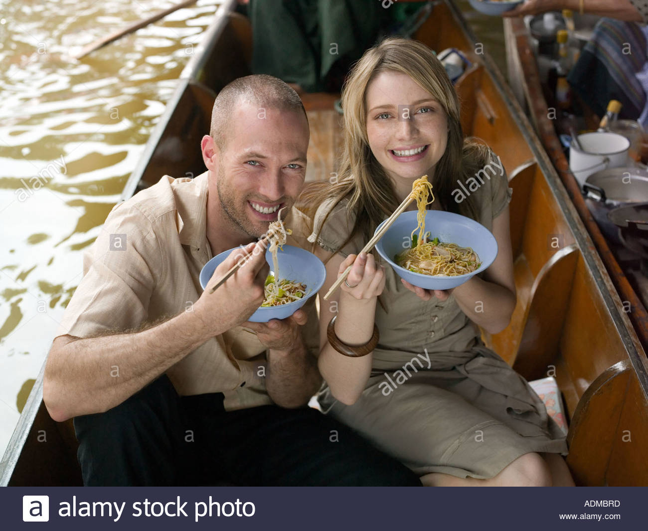 Couple eating meal on river boat - Stock Image