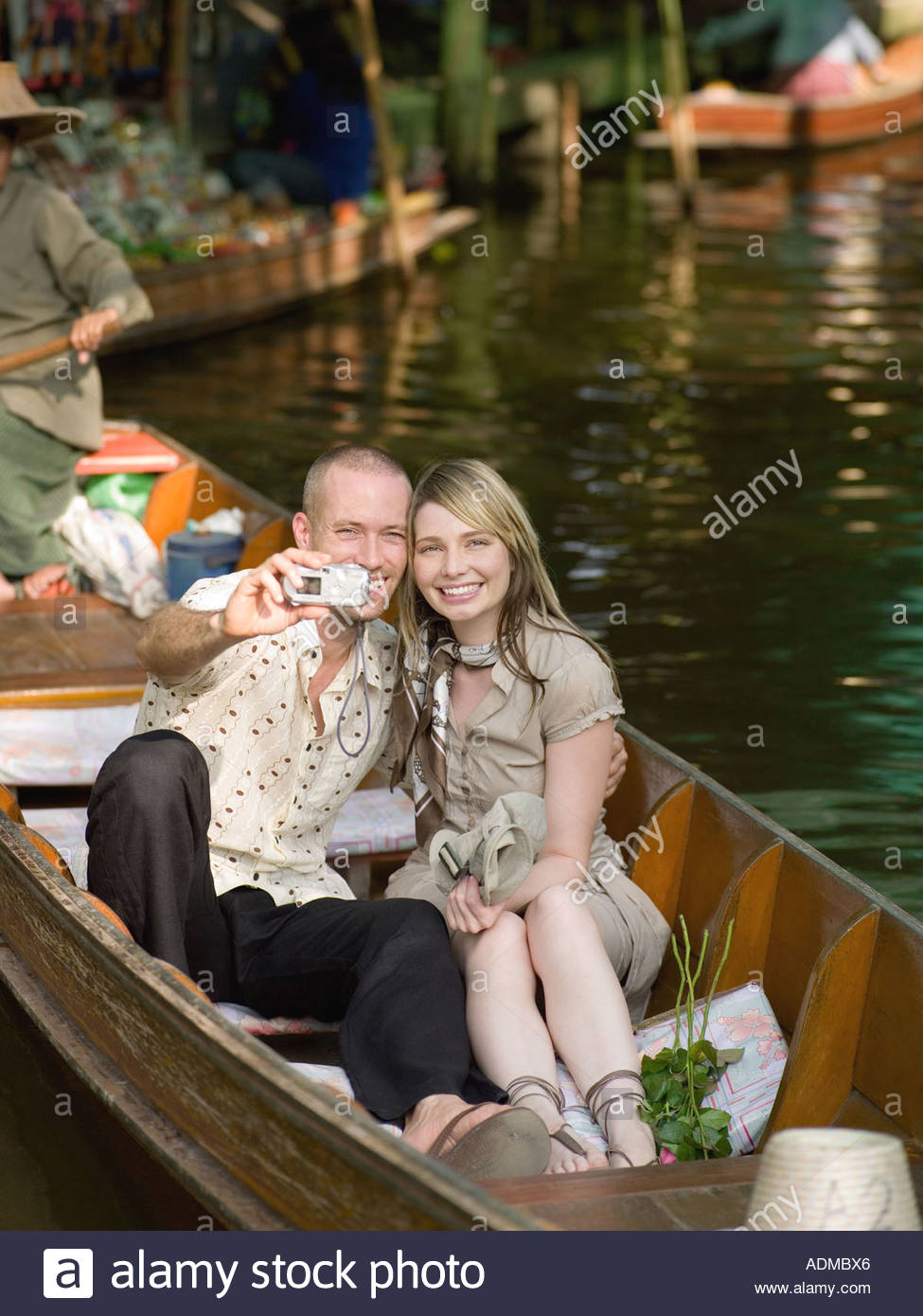 Couple taking a picture in a row boat - Stock Image