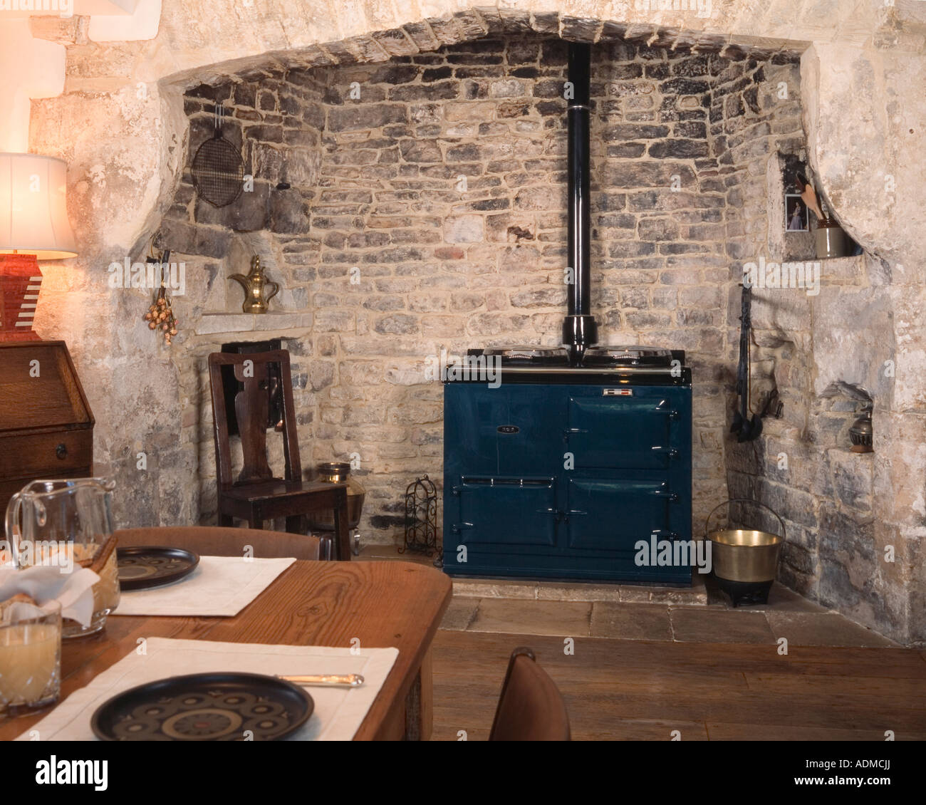 Domestic interior kitchen  old stone fieplace and aga cooker Stock