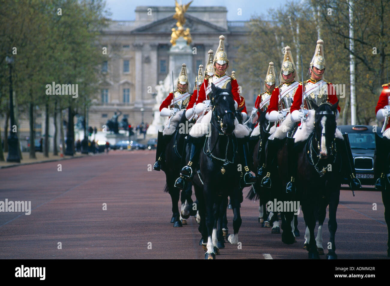 the Household Cavalry the Life Guards riding up the Mall with Buckingham Palace beyond London UK - Stock Image