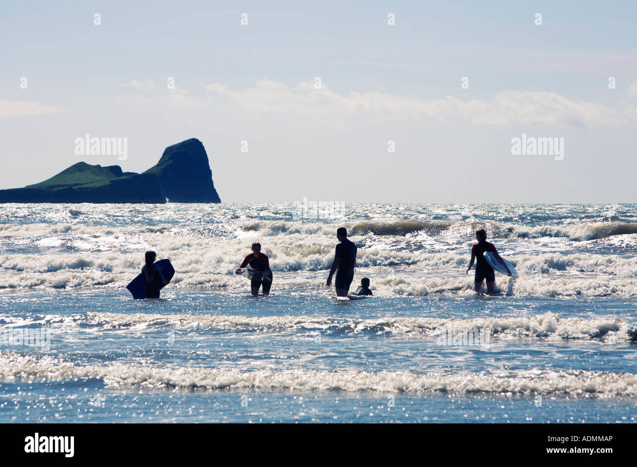 Family Body Boarding at Rhossili Beach with Worm Head Penrhyn gwyr in the Background Gower Swansea South Wales - Stock Image