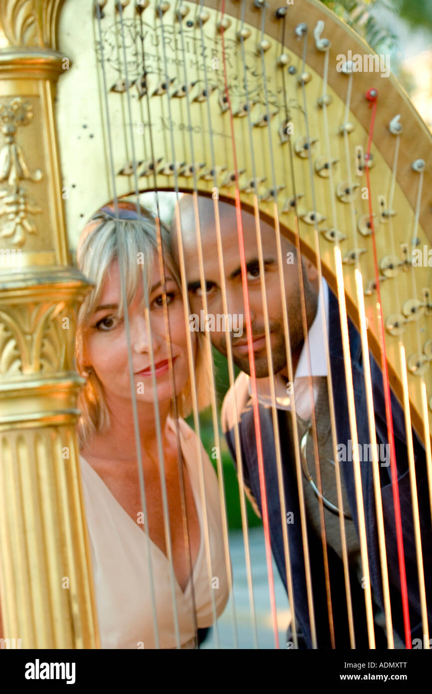 Black man and a white woman with harp in foreground - Stock Image