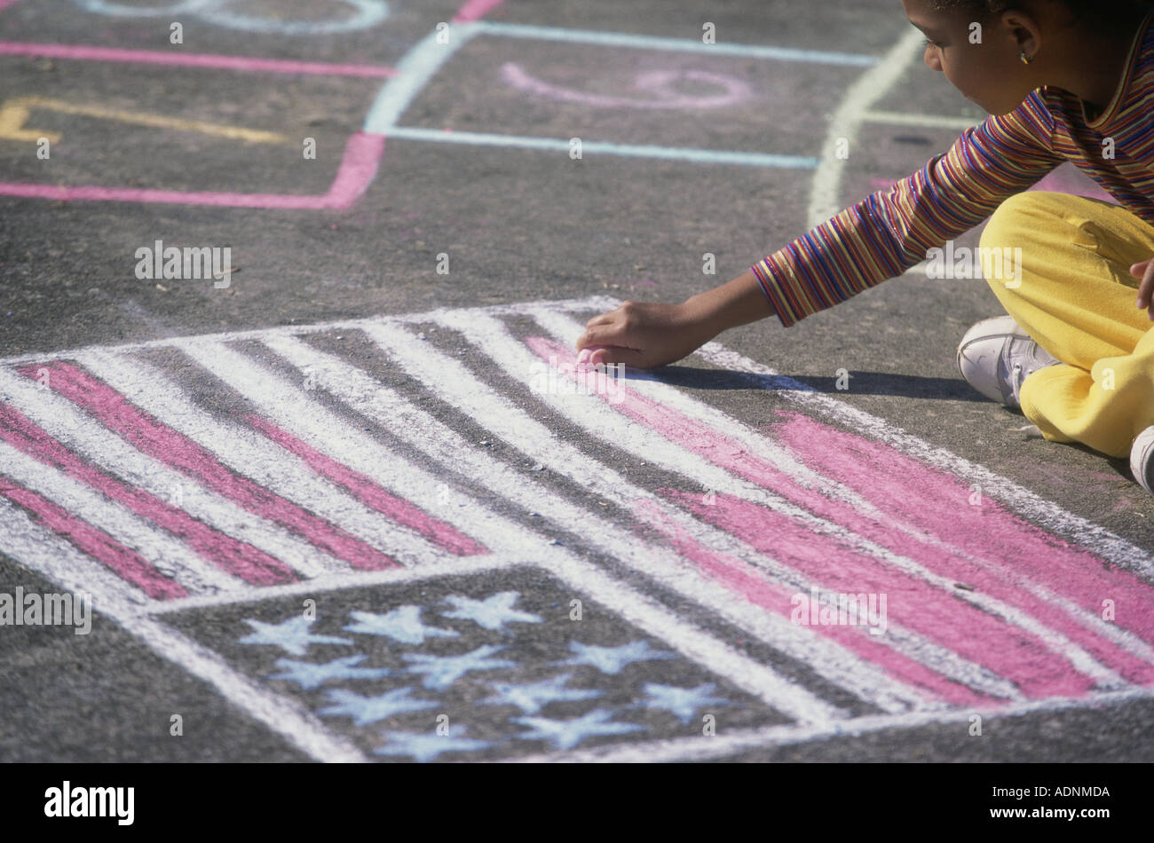 Girl drawing the American flag on the ground with chalk - Stock Image