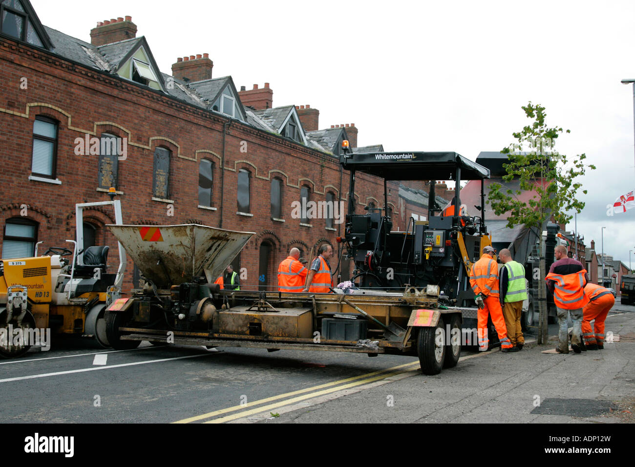 road resurfacing crew prepare equipment to resurface tarmac road in Belfast - Stock Image