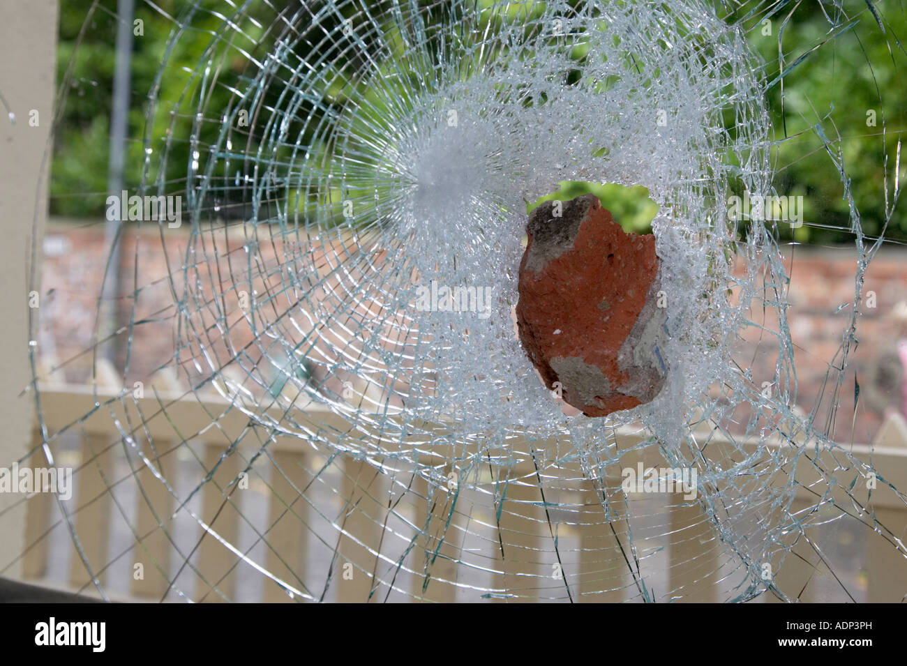 old red brick stuck in broken toughened strengthened glass window thrown by vandals in a hate crime looking out - Stock Image