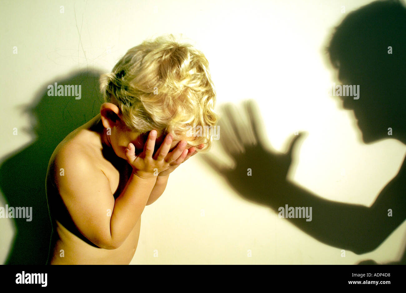 A tearful blonde child being threatened and the shadow of his abuser - Stock Image