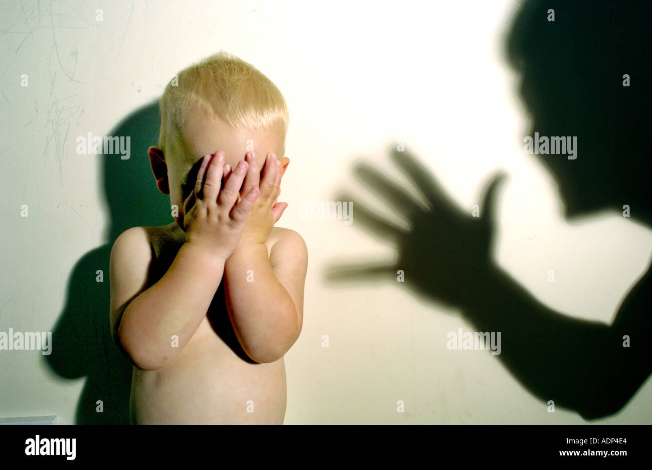 A terrified tearful child threatened with abuse with shadow of abuser looming over him - Stock Image
