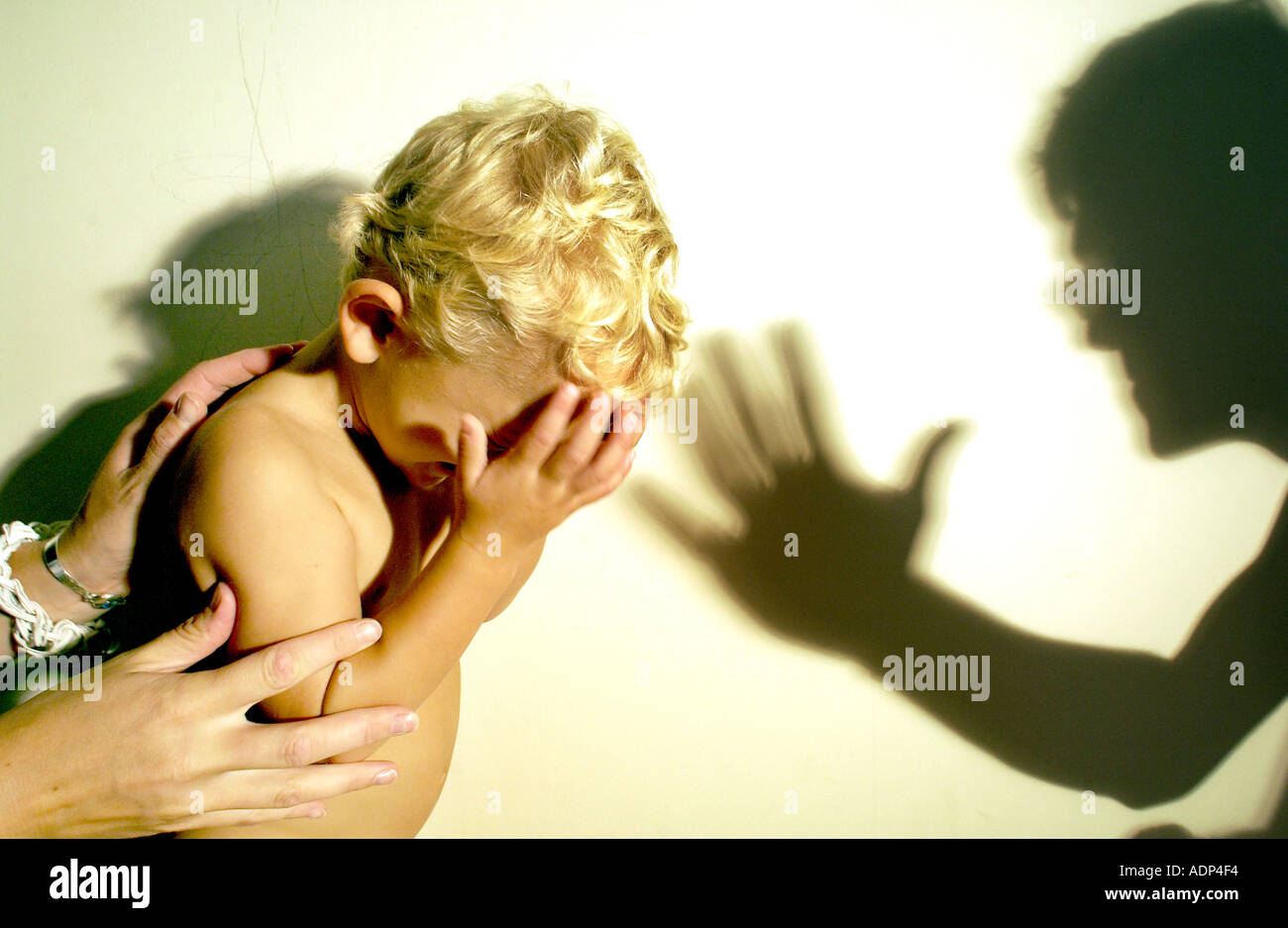 A terrified tearful child threatened with abuse being comforted by female hands and menaced by a man - Stock Image